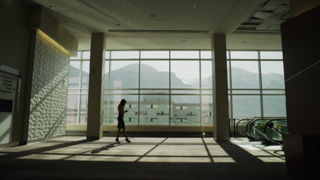 zooming shot of silhouetted businesswoman using cell phone and walking in lobby / provo, utah, united states,  - provo stock videos & royalty-free footage