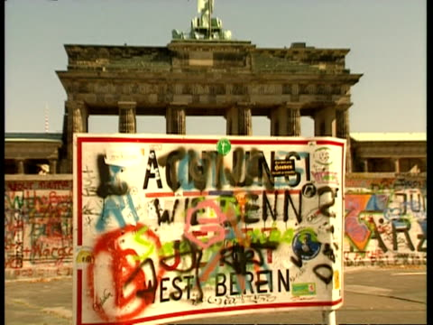 CU zooming to WA, Sign obscured by messy colourful graffiti, Brandenburg Gate and Berlin Wall in background, Berlin