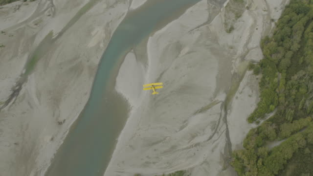zooming-in shot of a tiger moth airplane flying above a braided river - 複葉機点の映像素材/bロール