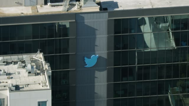 zooming-out shot of the twitter sign on the side of the headquarters building at the market street - messaggistica online video stock e b–roll