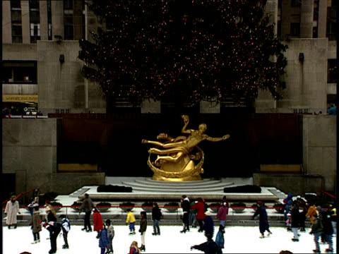 vídeos y material grabado en eventos de stock de zoomout from a gilded statue of prometheus to holiday ice skaters enjoying the rockefeller center skating rink in new york - árbol de navidad del centro rockefeller