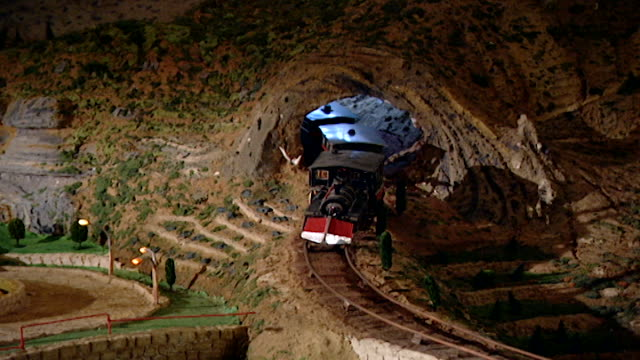 zoom-out from miniature electric train coming out of a tunnel, on maquette of a chouf mountain scene, displayed at the irfan school museum in the... - roundabout stock videos & royalty-free footage