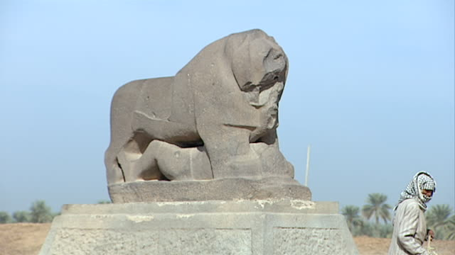 zoom-out from the lion of babylon to a man sweeping the ground with a palm frond. since the 2003 gulf war occupying forces have caused irreparable... - frond stock videos & royalty-free footage