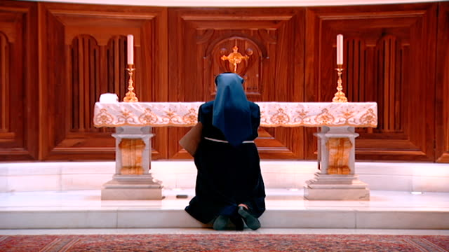 zoom-out of a maronite nun kneeling at altar in the maronite cathedral of saint george, located in downtown beirut. - apse stock videos & royalty-free footage