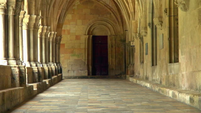 zoom-out of view of hallway of tarragona church - arco architettura video stock e b–roll