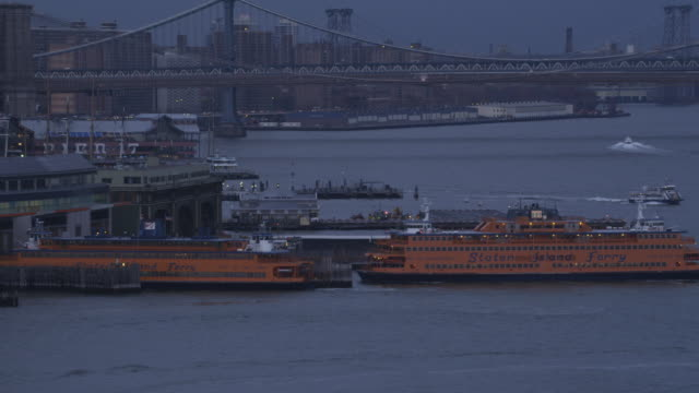 Zoom-out on Staten Island Ferry approaching dock at dusk with Brooklyn Bridge in background, Hudson River and Battery Park in foreground. Shot in 2011.