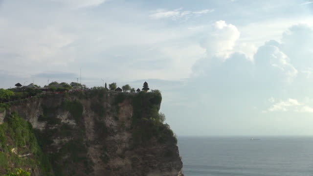zoom-out: uluwatu temple on cliff - temple building stock videos & royalty-free footage