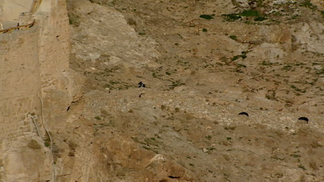 zoomout view of a man climbing up steep stairs cut into rock on his way to the monastery of saint moses the abyssinian which is nestled on a craggy... - steep stock videos & royalty-free footage
