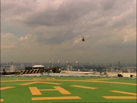 wa zooms out to show helicopter flying in sky and coming in to land, bangkok, thailand - helicopter landing pads stock videos and b-roll footage