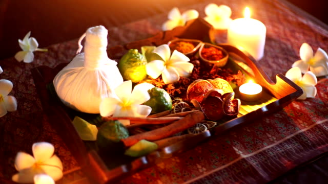 Zoon in A set of herbal treatments and herbal ball for massage and spa decorated with Frangipani and lighting candles.