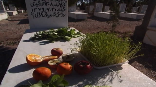 zoroastrian cemetery yazd. high-angle view of fruit and greenery left as offerings on a grave in the zoroastrian cemetery. - yazd province stock videos & royalty-free footage