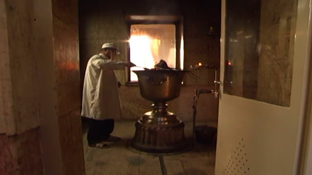 zoroastrian fire temple side view of a zoroastrian mobed or cleric keeping the sacred fire lit - side lit stock videos & royalty-free footage