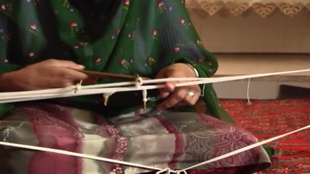 zoroastrian kushti weaver. view of a zoroastrian woman's hands weaving a kushti, a sacred girdle worn by zoroastrians. the kushti is made of 72 white... - weaving stock videos & royalty-free footage