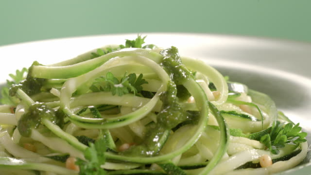 cu zucchini pasta on rotating dinner plate as pesto sauce is poured over the top and parmesan cheese sprinkled over top of pesto - courgette stock videos and b-roll footage