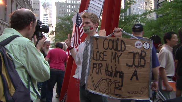 """zuccotti park / liberty square / focus on protesters and hand-made signs / """"yes we camp!"""" t-shirt occupy wall street protests on october 09, 2011 in... - occupy protests stock videos & royalty-free footage"""