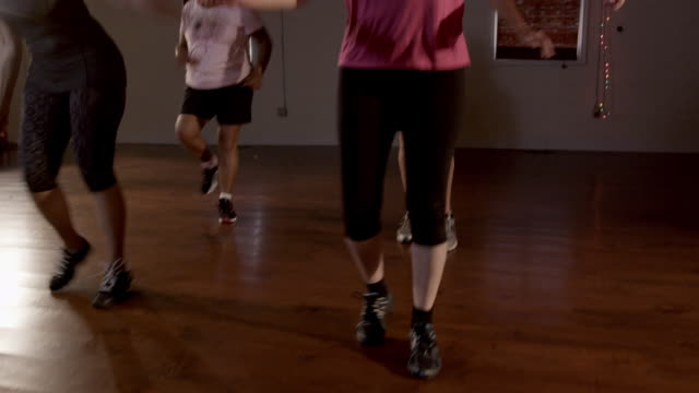 Zumba enthusiasts dance and turn as they exercise.